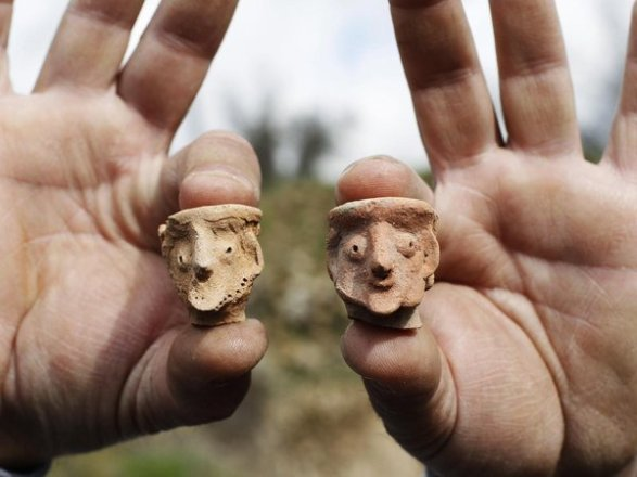 Baz Ratner / Reuters  An employee of the Israeli Antiquities Authority displays figurines at Tel Motza archaeological site on the outskirts of Jerusalem.